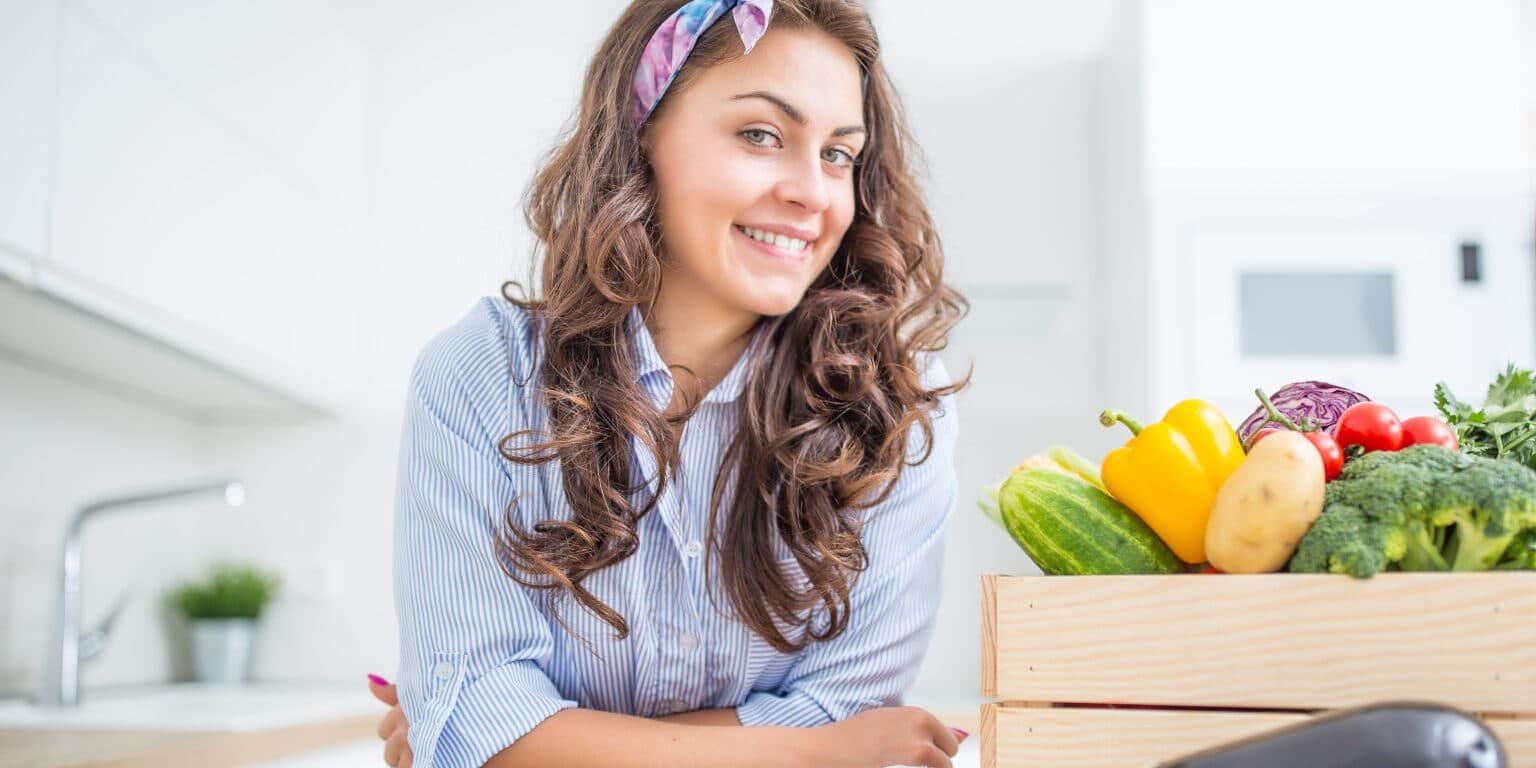 Woman in her kitchen with wooden box full of organic vegetable.